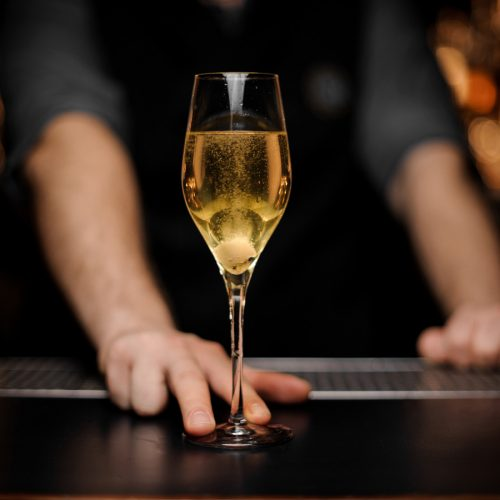 Close-shot-of-glass-with-sparkling-wine-in-the-bartender's-hands-1149484170_4117x2740