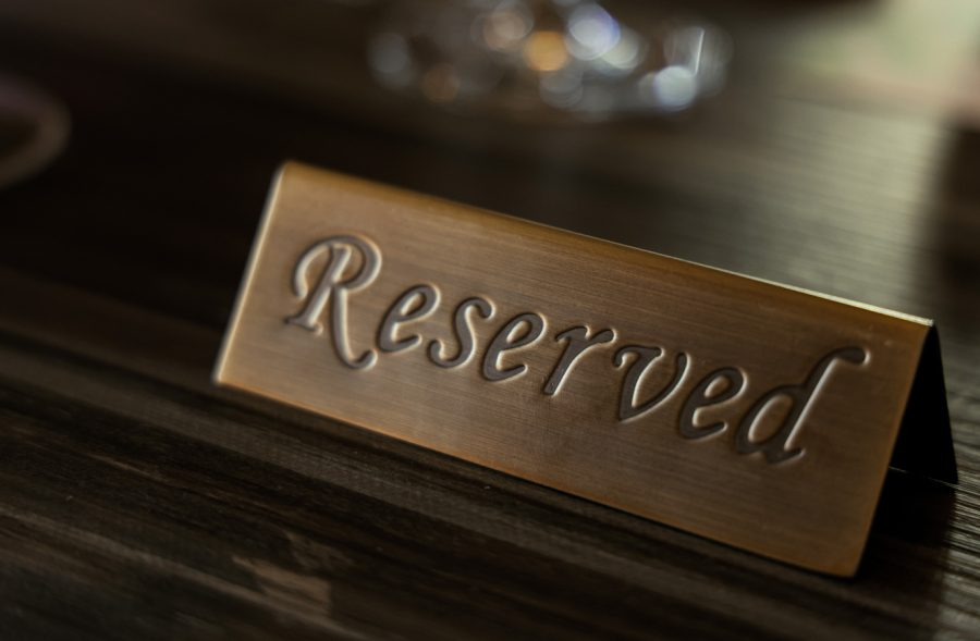 Reserved-plate-sign-on-wooden-table-at-restaurant-1327987328_7674x5118